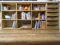 DIYで作ったカウンター下サイズピッタリの本棚と既存の木箱に合わせた棚